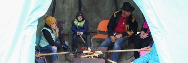 people cooking bannock in teepee
