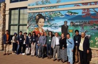japanese delegates in front of mural